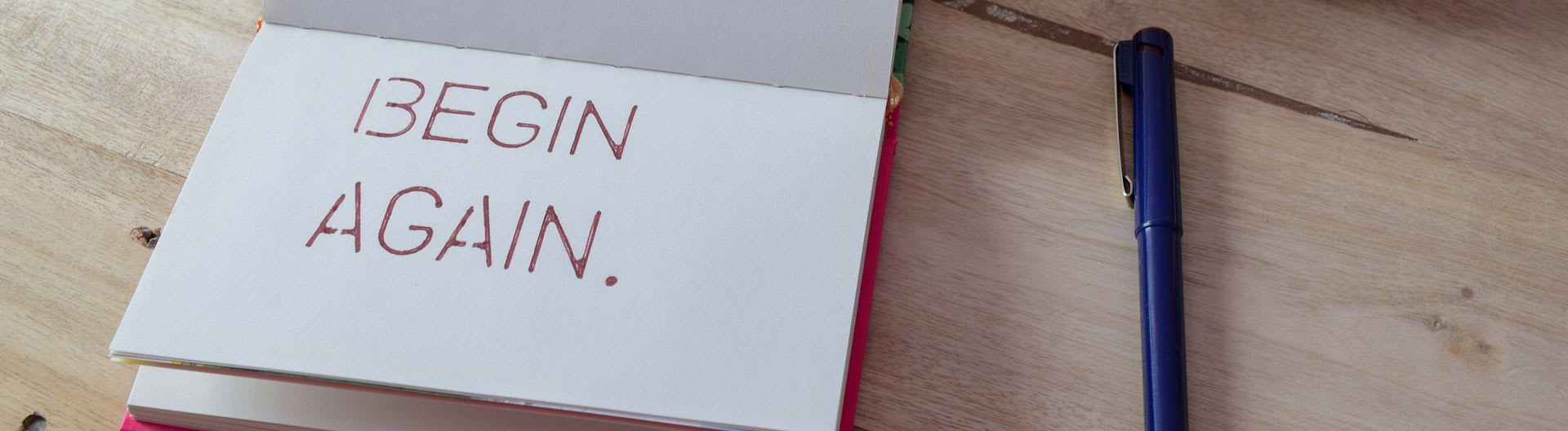 Notepad with the words begin again written on it